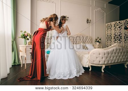 Gorgeous Bride In White Luxury Dress Is Getting Ready For Wedding.  Woman Putting On Dress. Stylish
