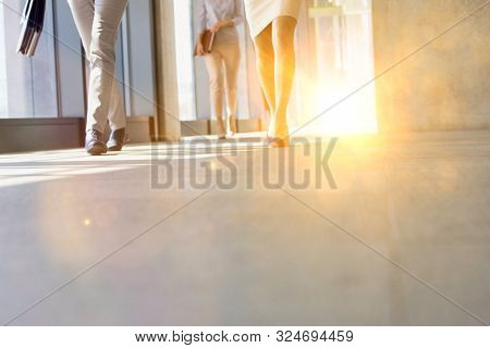 Business people walking in office corridor with yellow lens flare in background