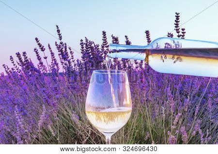 Lavender Wine. White Wine Poured Into A Glass Against A Lavender Field Background