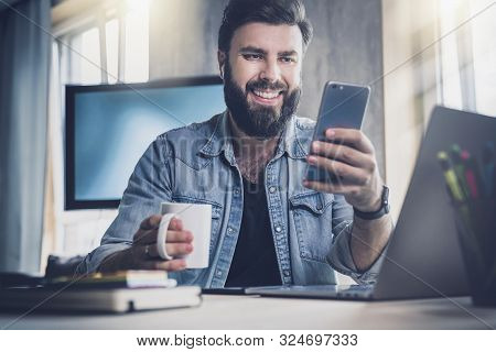 Manager Having Break In Office And Communicating With Online Friend In Social Network On Smartphone.