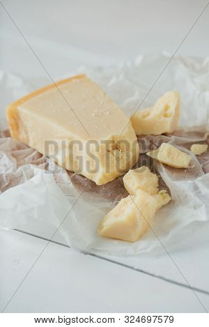 Italian Parmesan Cheese. Pieces Of Parmesan Cheese On White Wooden Table. Parmesan Cheese