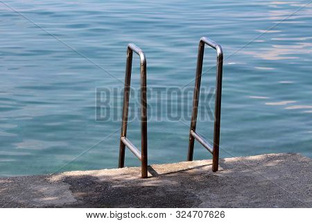 Two Inox Handrails For Easier Entrance From Concrete Beach To Calm Blue Sea On Warm Sunny Summer Day