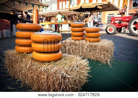 Holland Cheese Rounds Displayed On Hay Stack At Traditional Market. Food Background