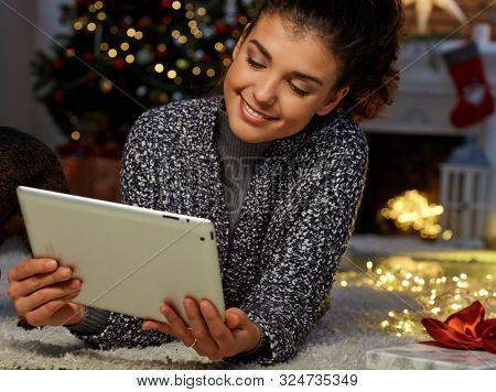 Woman shopping online at home in Winter. Happy young woman lying on floor using tablet and bank card for online shopping at home at Christmas time. Christmas tree and fireplace in background.