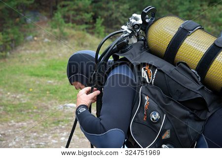 Paayanne Lake, Finland - September 2019. Diver Checks Equipment Near The Lake. Male Diver In Wetsuit