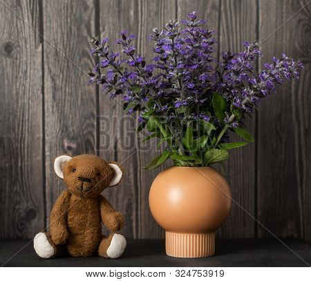 Cute Still Life With A Plush Teddy Bear And A Bouquet Of Purple Flowers On A Wooden Background. Vint