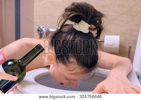 Drunk Young Woman Is Vomiting In Toilet Sitting On The Floor With Wine Bottle In Hand At Home, Morni