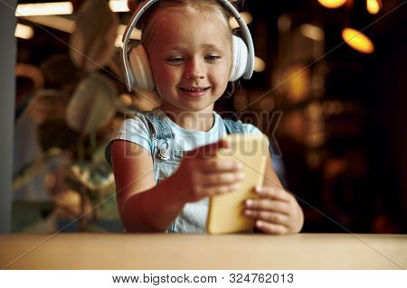 Little Girl Using Smartphone And Looking Happy Stock Photo