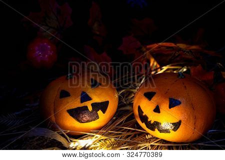 Two Funny Or Angry Pumpkins Jack O'lantern Head Look At Each Other, The Light Shines On Their Face,