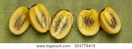 row of cut gold kiwifruit berries against green textured paper, long banner format