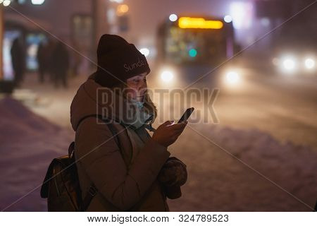 Young Woman Checking The Smartphone While Waiting For The Bus To Come. Froty Winter. Dusk Time.