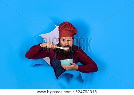 Healthy food. Eat healthy. Healthy ration. Chef wear hat and apron looking through paper hole. Man professional chef hold bowl and spoon. Dieting concept. Bearded chef in uniform. Cook preparing food poster