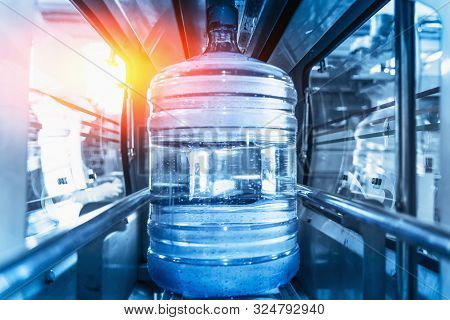 Plastic Bottle Or Gallon Of Purified Drinking Water Inside Automated Conveyor Production Line. Water