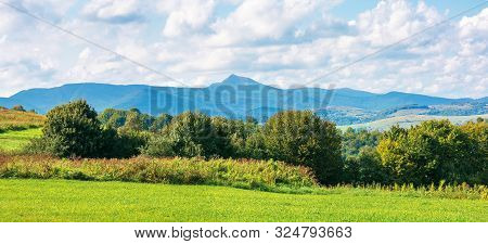 Mountain Ridge With High Peak. Sunny Weather In Early Autumn With Fluffy Clouds On The Sky. Trees On