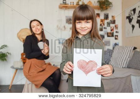 Caucasian Little Girl Gives Drawing To Mother. Mothers Day Or Birthday Concept.