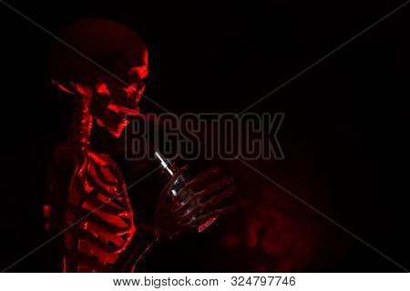 Skeleton Vaping Clouds Of Red Highlighted Vapor In The Dark With An Ecigarette