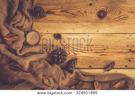 Autumn Background. A Cup Of Hot Coffee, Knitted Scarf And Pinecones On Wooden Table. Autumn Coffee.