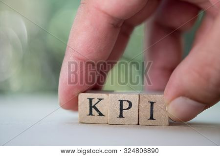 Businessman Hand Holding Wooden Cube Block With Kpi: Abbreviation Of Key Performance Indicator. Kpi