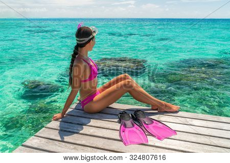 Beach vacation sport girl ready to snorkel in coral reefs of perfect turquoise waters in Tahiti, French Polynesia. Active watersport travel lifestyle adventure snorkeling trip.