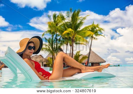 Luxury pool vacation woman sunbathing in lounging chair of high end hotel swimming pool holiday resort for summer getaway. Lady with sun hat and red swimsuit in water lounger.