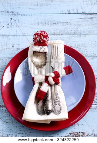 Christmas Table Setting With Holiday Decorations In The Form Of A Knitted Hat And Scarf In White And