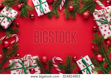 Red Christmas and New Year background. Decorative frame of fir branches, gifts, Christmas balls and candy cane. Copy space for Christmas creep