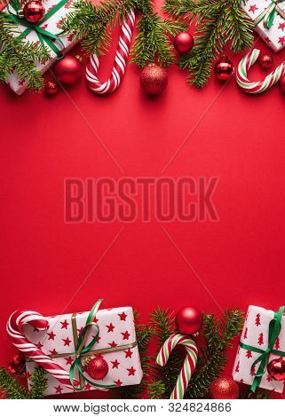Red Merry Christmas and New Year background. Decorative border of fir branches, gifts, Christmas balls and candy cane. Christmas creep