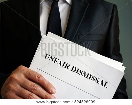 Unfair Dismissal Concept. Man Is Holding Stack Of Papers.