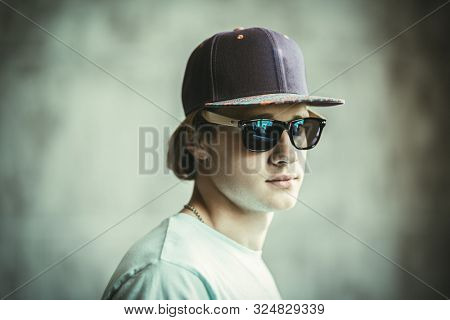 A portrait of a young goodlooking man in a cap posing indoor. Casual men fashion, beauty, optics.