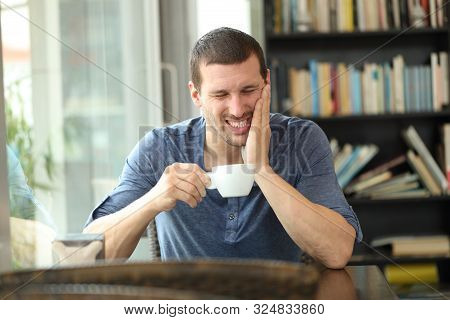 Fronf View Portrait Of A Man Complaining Suffering Tooth Ache After Drinking Hot Beverage Sitting In