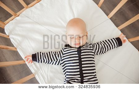Cute Baby Boy Lying In Wooden Crib Or Cot