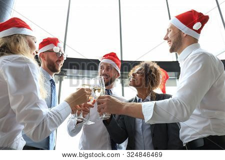 Office Business Coworkers Celebrating Winter Holidays Together At Work And Drinking Champagne In Off