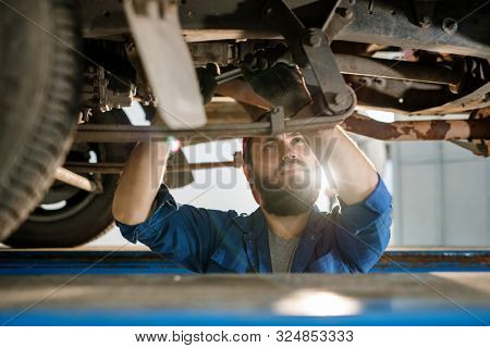 Serious male technical engineer of car repair service looking at one of details while standing under machine