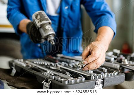 Mature technician or repairman taking one of iron nozzles for technical drill while standing by open kit of worktools