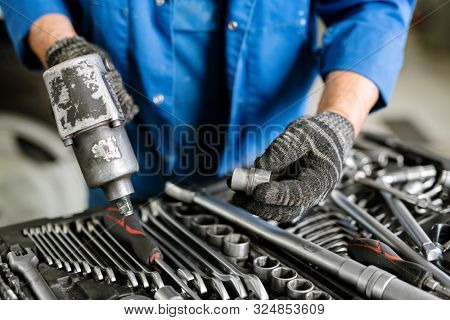 Gloved engineer of contemporary machine repair service holding worktool while choosing proper nozzle