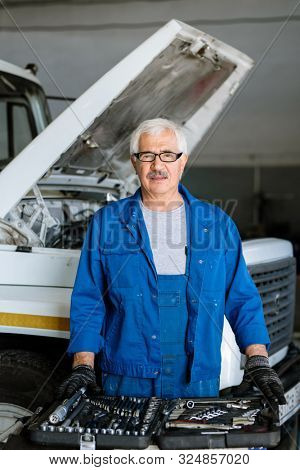 Mature technician with grey hair choosing worktools while serving one of broken machines in his workshop