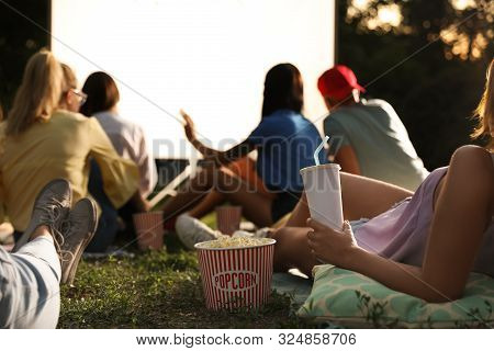 Young People With Popcorn And Drink Watching Movie In Open Air Cinema, Closeup