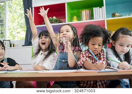 Group Of Little Preschool Kids Drawing Paper With Color Pencils . Portrait Of Children Friends Educa