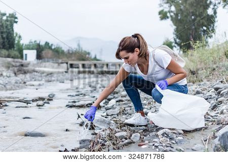 Stock Photo Of A Girl With Blue Gloves Crouched On The Bank Of The River Taking Plastic Out Of The W