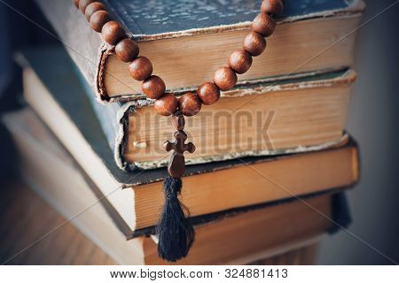 The Sacred Rosary, Made Of Mahogany, Lies On A Pile Of Old Battered Books In Which Religious Precept