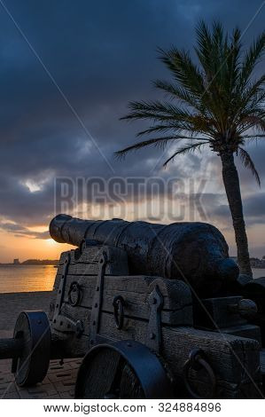 Old Cannon On Wooden Gun Carriage On The Promenade In The Harbor On Cloudy Sunset And Palm Tree Back