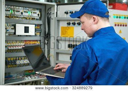 Electrician measures electrical paramenters with tester multimeter equipment at electrical fusebox or switch box