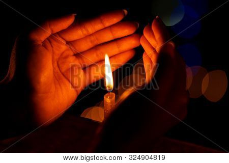 Female Hand Holding Or Protecting Candle From Wind At Diwali Celebration Night. Background Stock Pho