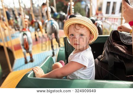 Cute Blonde Little Girl With Curls In A White T-shirt In A Vintage Straw Hat Rides On A Carousel. Be