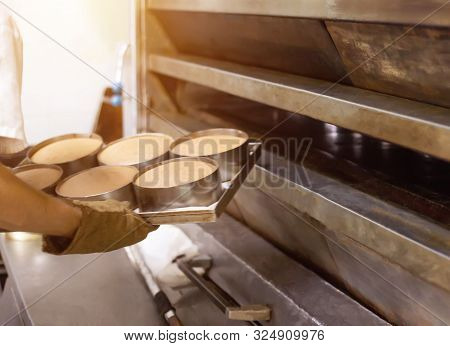 A Male Cook Takes Out Bread From A Hot Oven At A Bakery, Industry