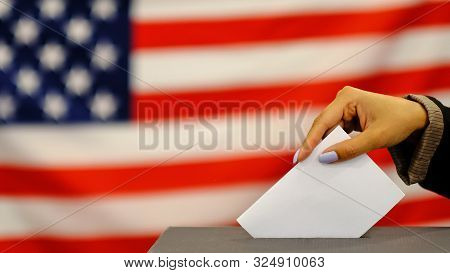Woman Putting A Ballot In A Ballot Box On Election Day. Close Up Of Hand With White Votes Paper On U