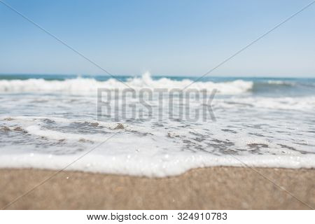Beautiful Blue Sky Over A Restless Sea With Waves With White Foam. Living Sea With Clear Sky On The