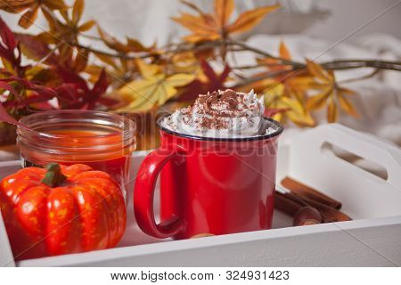 Red mug of hot creamy cocoa with froth on the wooden white tray with cookies, autumn leaves, candle and pumpkin on the background poster