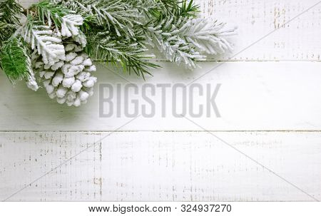 Christmas tree branch and pine cone in snow on a white wooden background. Winter festive concept. Flat lay, copy space.
