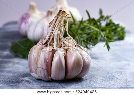 Whole Violet Garlic Bulbs And Fresh Kitchen Herbs Close Up On Grey Marble Plank